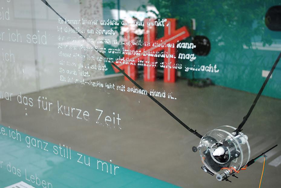 Ein Zeichenroboter am Fenster der vier.zentrale schreibt, was die KI ihm vorgibt / Foto: Caroline Zirves
