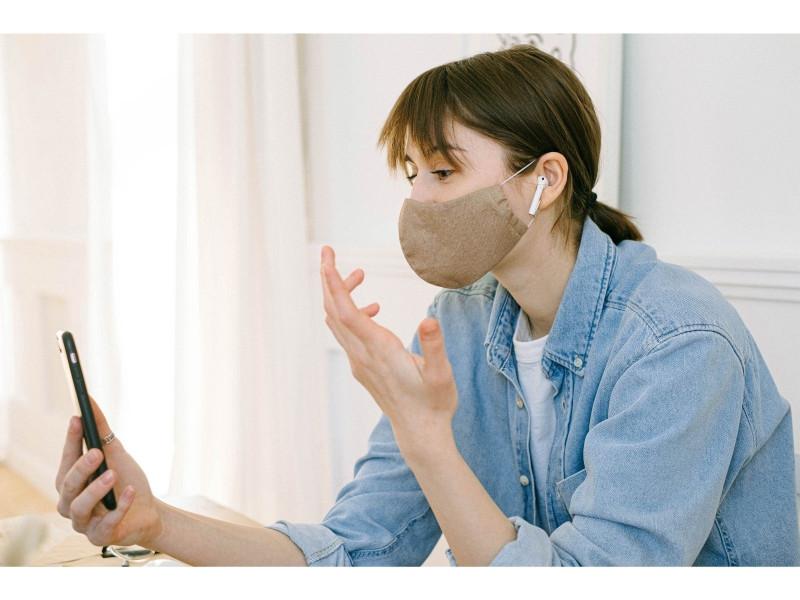 Corona-Coaches: Das Foto zeigt eine junge Frau mit Schutzmaske auf bei einem Video-Call mit dem Handy - Quelle: Canva
