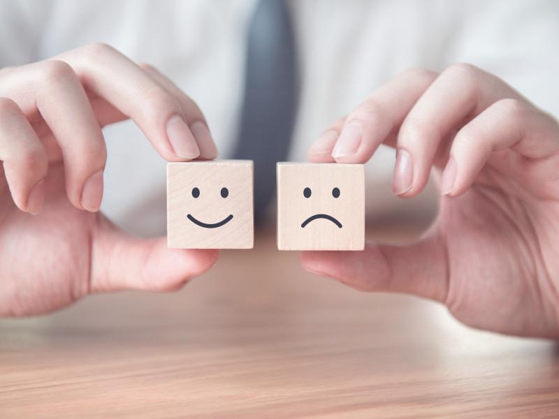 Zwei Hände halten zwei Holzklötzchen; eines mit einem lachenden Smiley und eines mit einem negativ schauenden, traurigen Smiley drauf. (Foto: Canva)