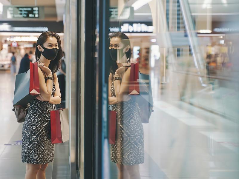 Auf dem Foto steht eine Frau in einem Einkaufscenter mit einer Maske im Gesicht und einer Shopping-Tüte in der Hand. Sie blickt dabei in ein sich spiegelndes Schaufenster. (Quelle: Canva)
