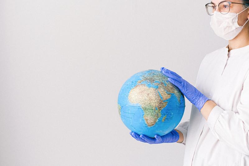 Eine Person im Arztkittel mit einer Gesichtsmaske und Latex-Handschuhen hält einen Globus. Foto: Canva