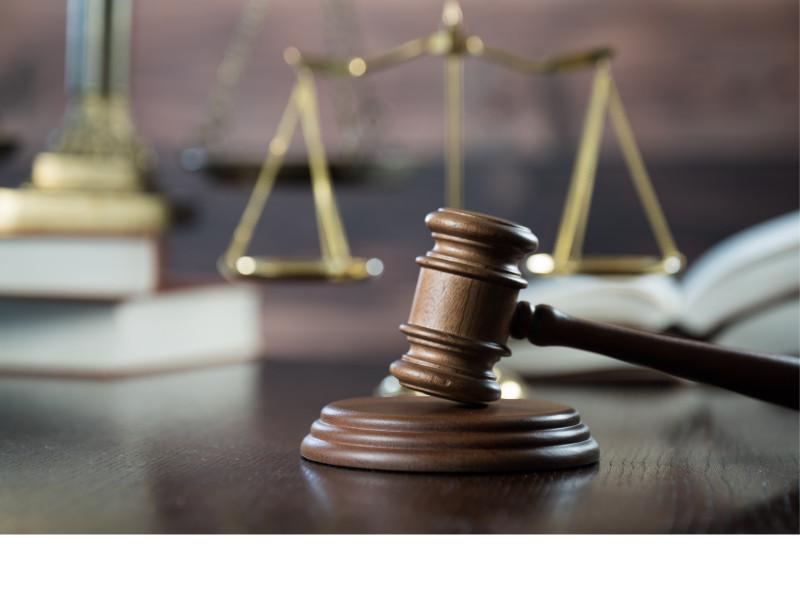 Das Foto zeigt im Vordergrund einen Gerichtshammer zur Urteilssprechung, im Hintergrund sind eine goldene Waage und mehrere Bücher verschwommen abgebildet. Quelle/Autor: Canva