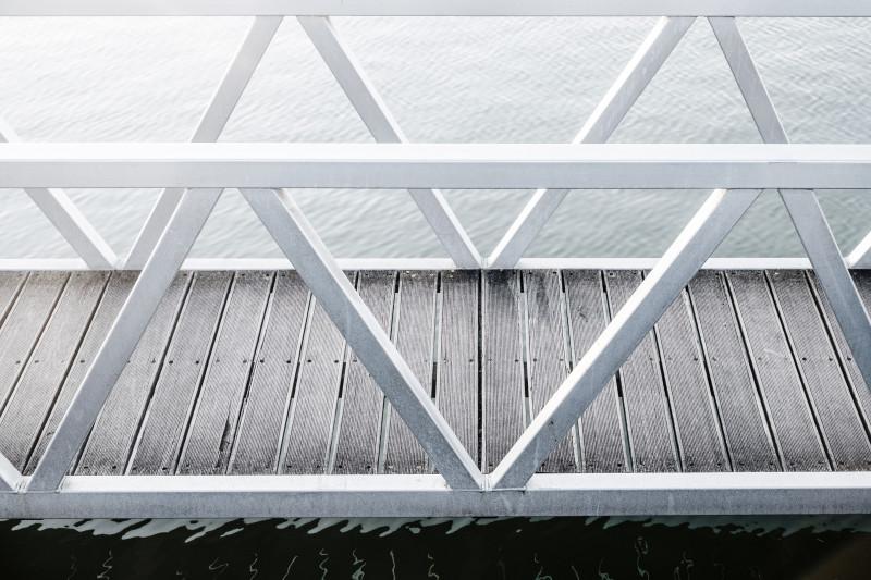 Das Foto zeigt den Ausschnitt einer weißen Holzbrücke, die über ein Wasser führt.