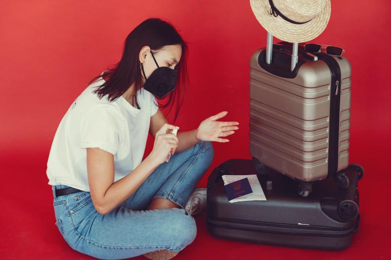 Junge Reisende sitzt mit ihren zwei Koffern und einem Mund-Nase-Schutz auf dem Boden vor einem roten Hintergrund und desinfiziert ihre Hände